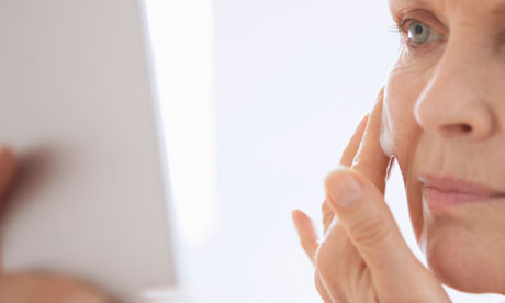 A mature woman applying cream to her cheek Photograph: John Slater/Getty ...