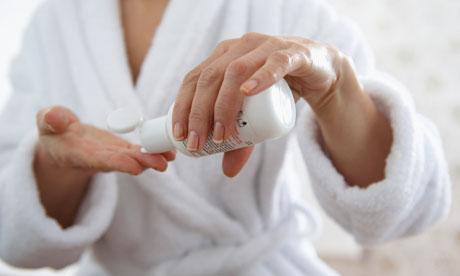 A mature woman applying moisturiser