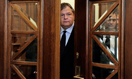 Greek Finance Minister Evangelos Venizelos stands behind a door during a cabinet meeting in Athens