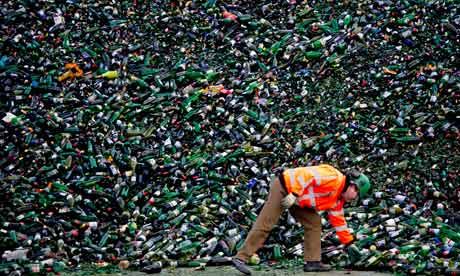 An employee at Maltha glass recycling with an enormous amount of bottles