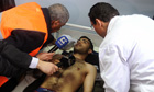 An Arab league observer listens to a Syrian injured man