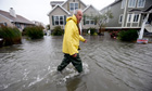 Richard Thomas walks through flood water in front of his home in Fenwick Island