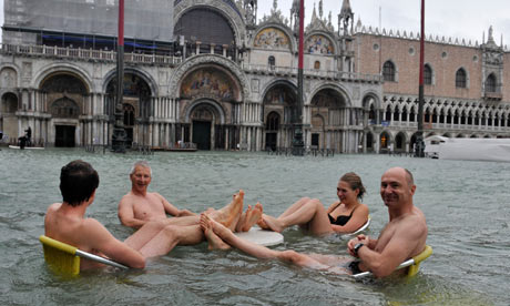 People sit at a table in flooded St Mark's Square in Venice, Italy