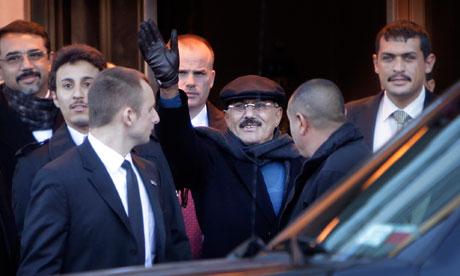 Yemeni President Ali Abdullah Saleh waves to protesters as he leaves his hotel in New York