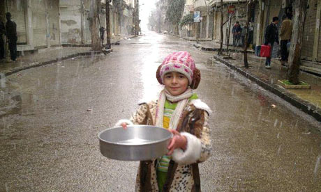 A girl collects rainwater during a heavy shower in Bab Seba'a, Homs