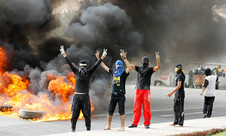 Anti-government protesters flash victory signs as they burn tyres in Budaiya, Bahrain