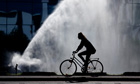 A woman cycles past a water sprinkler in Berlin