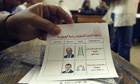 An Egyptian electoral official holds a ballot paper as a woman arrives to cast her vote