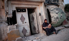 A Syrian woman sits with her grandson outside a damaged building in Tremseh, Syria