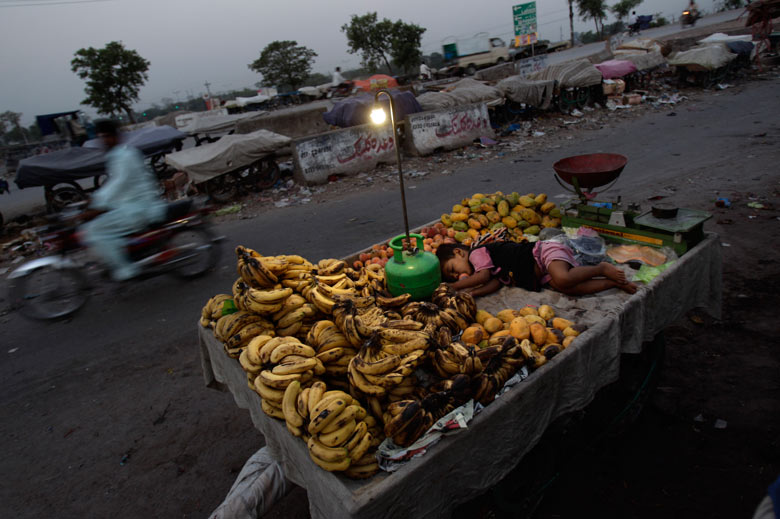 The son of a fruit vendor sleeps on his father's cart at a roadside on the outskirts of the city