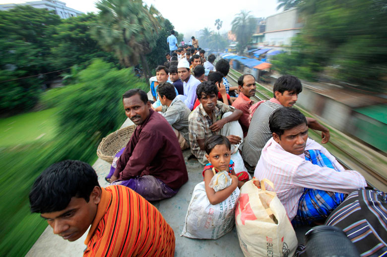 Passengers sit on top of an overcrowded train before the Eid al-Fitr holiday