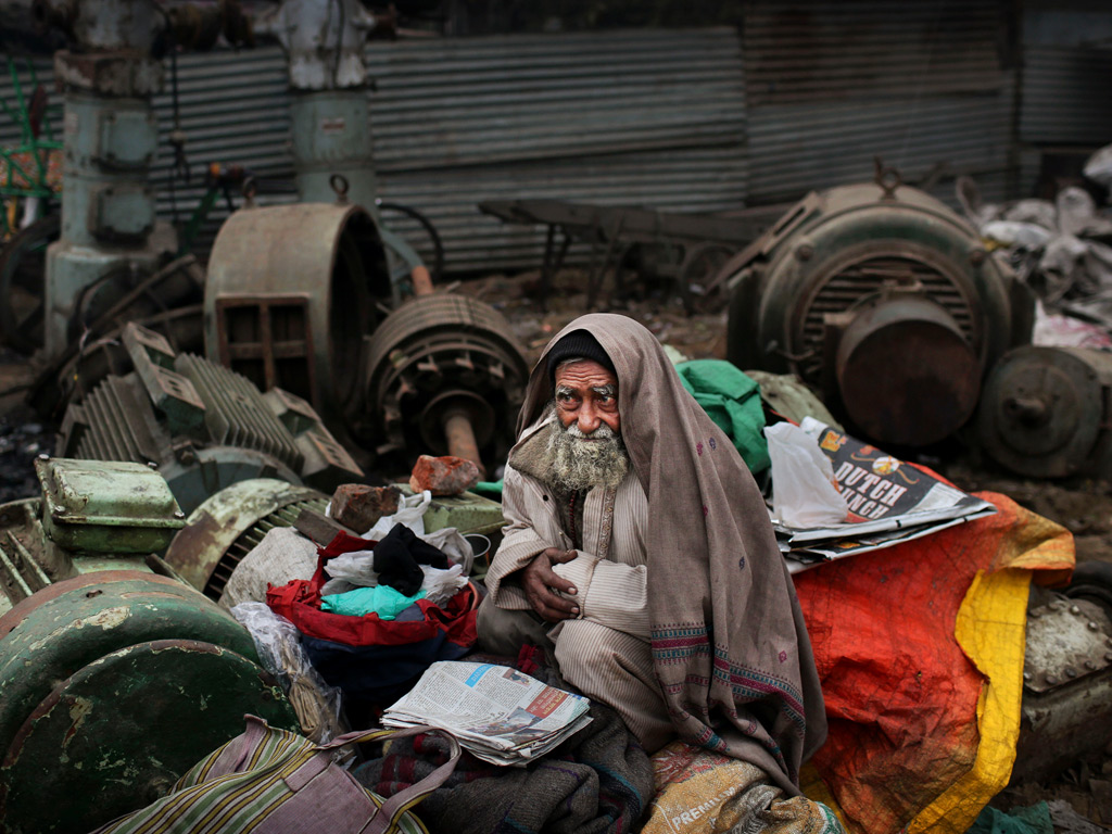 A ragpicker seeks warmth on a chilly day as northern India continues to face low temperatures