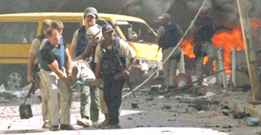Security personnel carry a victim of one of two bomb attacks in Baghdad. Photograph: Akram Saleh/Reuters