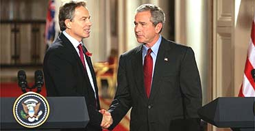 George Bush and Tony Blair shake hands during their White House news conference