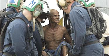 An injured man is carried from a US Navy helicopte
