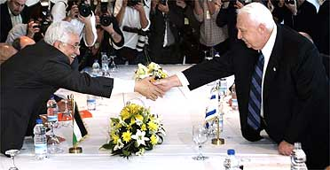 Israeli Prime Minister Ariel Sharon, right, and Palestinian Authority President Mahmoud Abbas shake hands