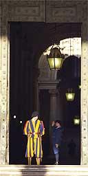 A Swiss guard looks down at the Vatican bronze door entrance