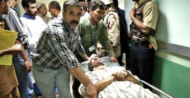 An injured Iraqi man is taken to hospital after car bomb explosions in Baghdad on April 29 2005