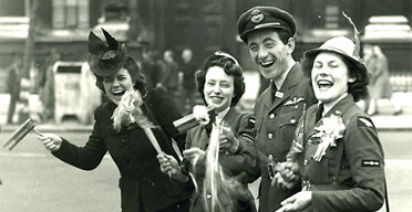 In Whitehall, London, an RAF officer and two members of the Women's Royal Air Force and a civilian celebrate on VE Day 1945
