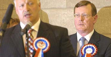 David Simpson (left) speaks after defeating Ulster Unionist leader David Trimble (right) in the election for the Upper Bann seat