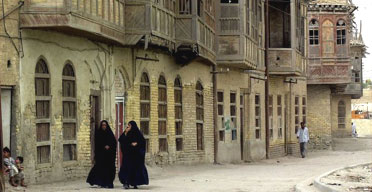 Two Iraqi women walk through the old part of Basra, southern Iraq. Photograph: Samir Mizban/AP