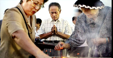 Elderly women burn incense sticks while a man offers prayers before the cenotaph for the victims of Hiroshima's nuclear attack in Peace Memorial Park in Hiroshima. Yoshikazu Tsuno/AFP/Getty