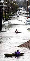 New Orleans residents wade and paddle through a flooded street.