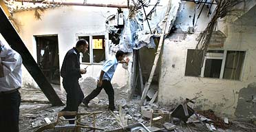 Palestinian police inspect a damaged home hit during an Israeli missile strike in Khan Yunis