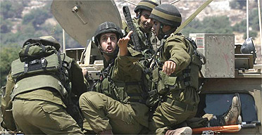Israeli soldiers approach the border with Lebanon