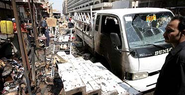 An Iraqi man inspects the site of a roadside bomb explosion at Shurja market, Baghdad