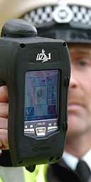 A police officer holds a portable finger print analyser at the launch of the device.