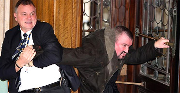 Michael Stone is restrained by security staff after forcing the suspension of the Stormont assembly