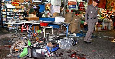 A Thai police officer inspects a bomb blast scene at a market in central Bangkok