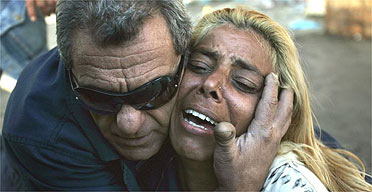 An Israeli woman is comforted by a friend at the site of a suicide bombing in the southern city of Eilat