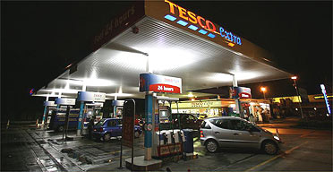 Drivers fill up at a Tesco petrol station. Trading standards officers are launching an investigation into claims that garages are selling contaminated fuel