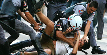 Brazilian police beat a protester during a march against US president George Bush in Sao Paulo.