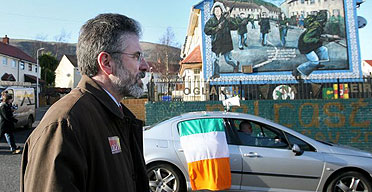 Sinn Fein president Gerry Adams passes a republican mural in the Ballymurphy area of Belfast , Northern Ireland.