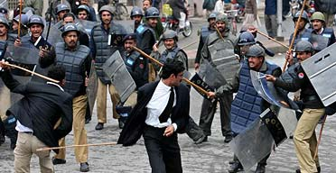 Baton-wielding police officers break up a demonstration on the main street in Lahore