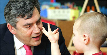 Gordon Brown talks to a young child in a nursery