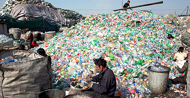 Migrant workers sort waste for recycling in China
