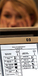 A woman views a monitor displaying ballot papers scanned by automatic machines for the Scottish elections