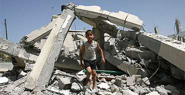 A Palestinian child walks on the rubble of a destroyed building at a Hamas sports club following an Israeli air strike in Beit Hanun, in the Gaza strip