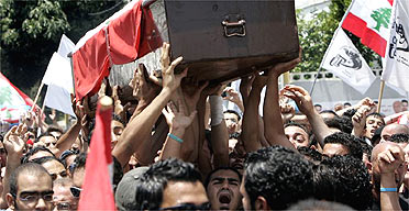Mourners carry the coffin of one of the bodyguards killed in the same bomb blast as Lebanese MP Walid Eido