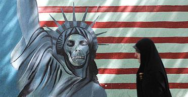 An Iranian woman walks past an anti-US mural in Tehran
