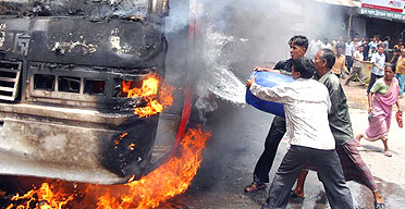 Local residents attempt to douse a bus set on fire during protests in Dhaka to demand an end to emergency rule