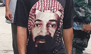 A man wearing a t-shirt with the picture of al-Qaida leader Osama bin Laden passes by a police officer in the southern Philippines
