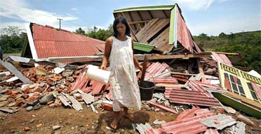 A Indonesian resident salvages items after an earthquake damaged her new house