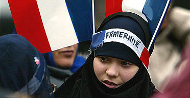 A Muslim girl has two French flags and a headband which reads