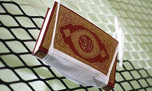 A Qur'an hangs from a cell's fencing in Camp Delta, Guantanamo Bay.