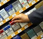 A tobacco seller reaches for a pack of cigarettes at a Paris shop. Photograph: Franck Prevel/AP